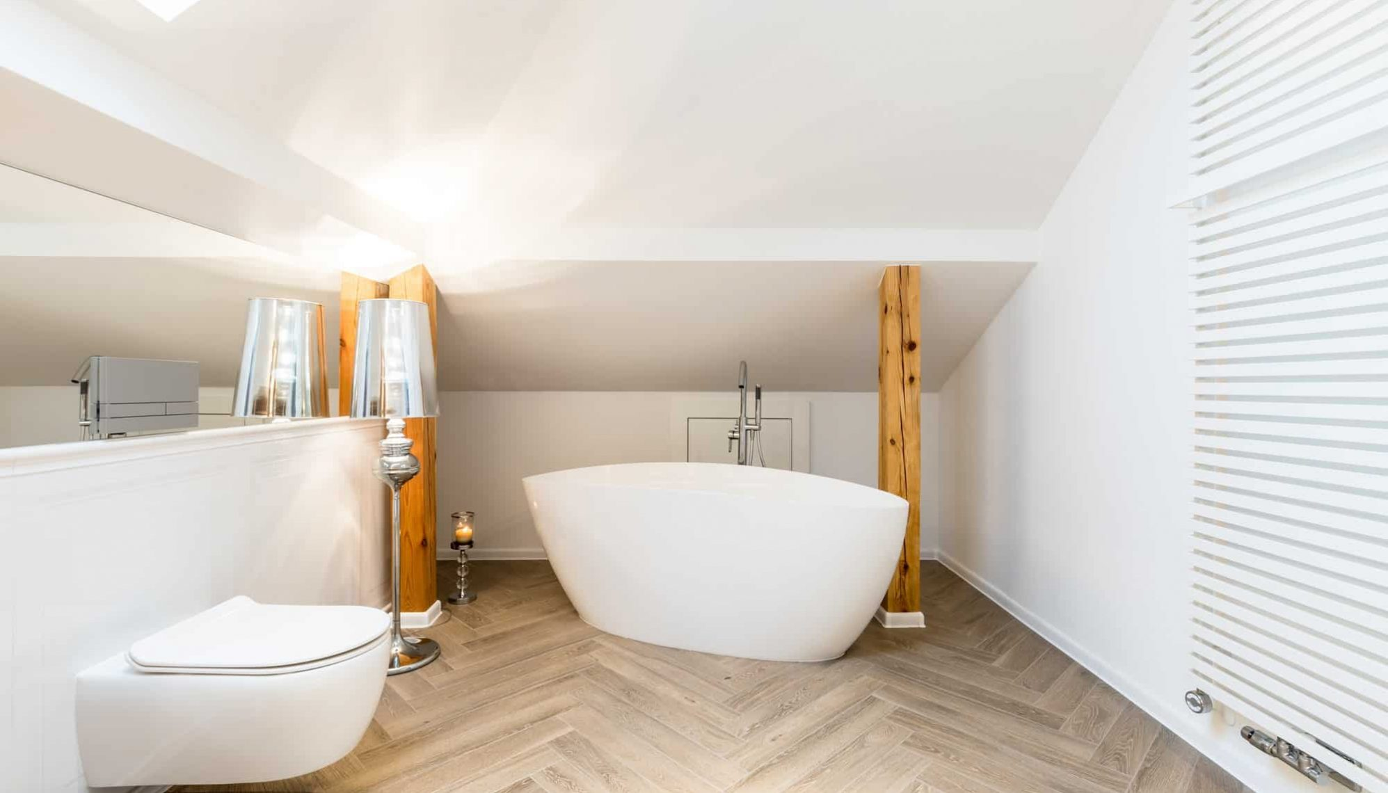 White attic bathroom with bathtub