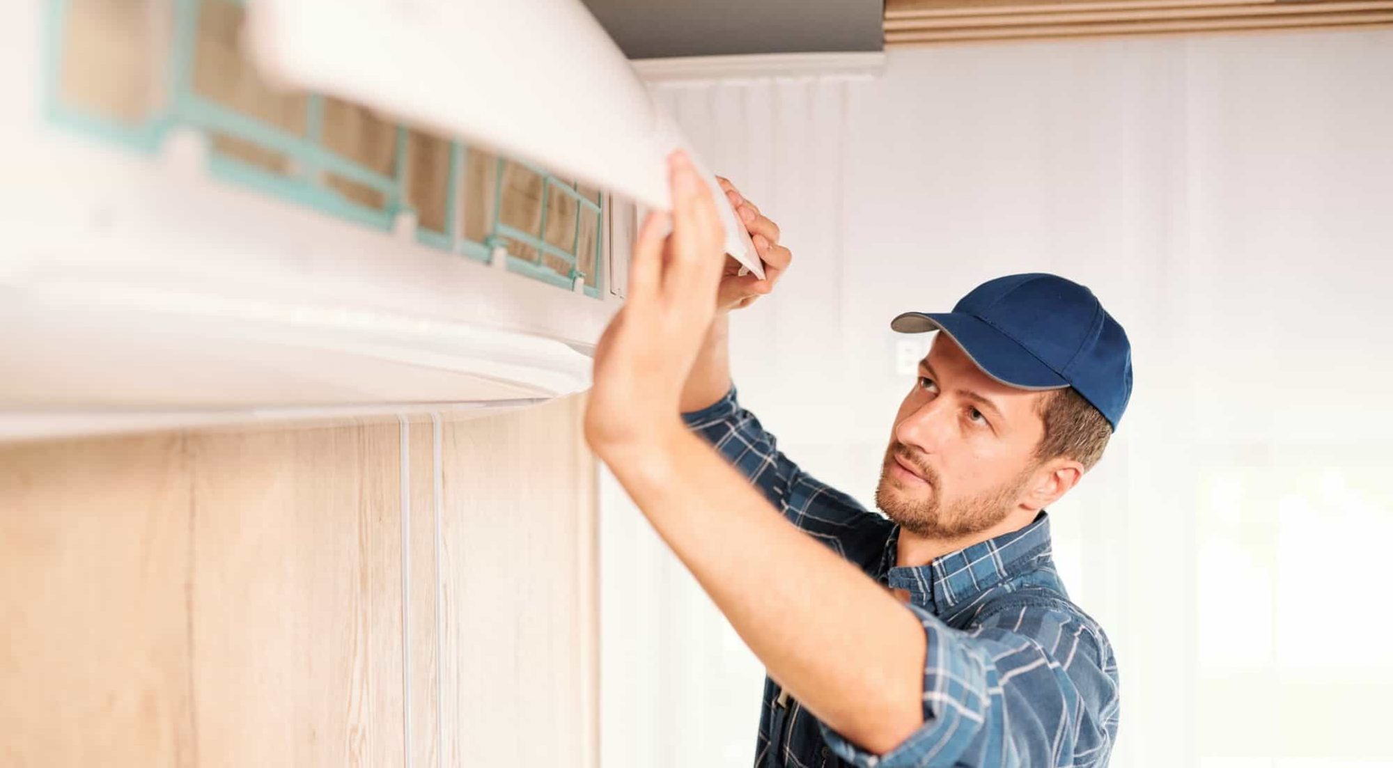 Young electrician or repiar service technician opening lid of air conditioner